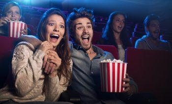 Young scared couple at the cinema watching an horror movie and screaming, she is holding her boyfriend's hand