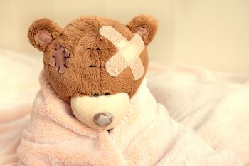 Sick teddy bear with patch in bed