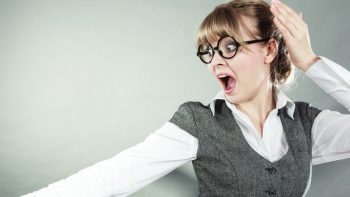 Business woman screaming looking shocked in full fear wide open mouth grey wall background.